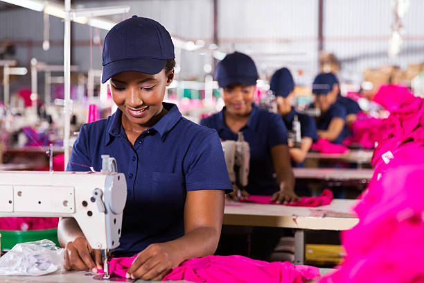 young african textile worker sewing stock photo