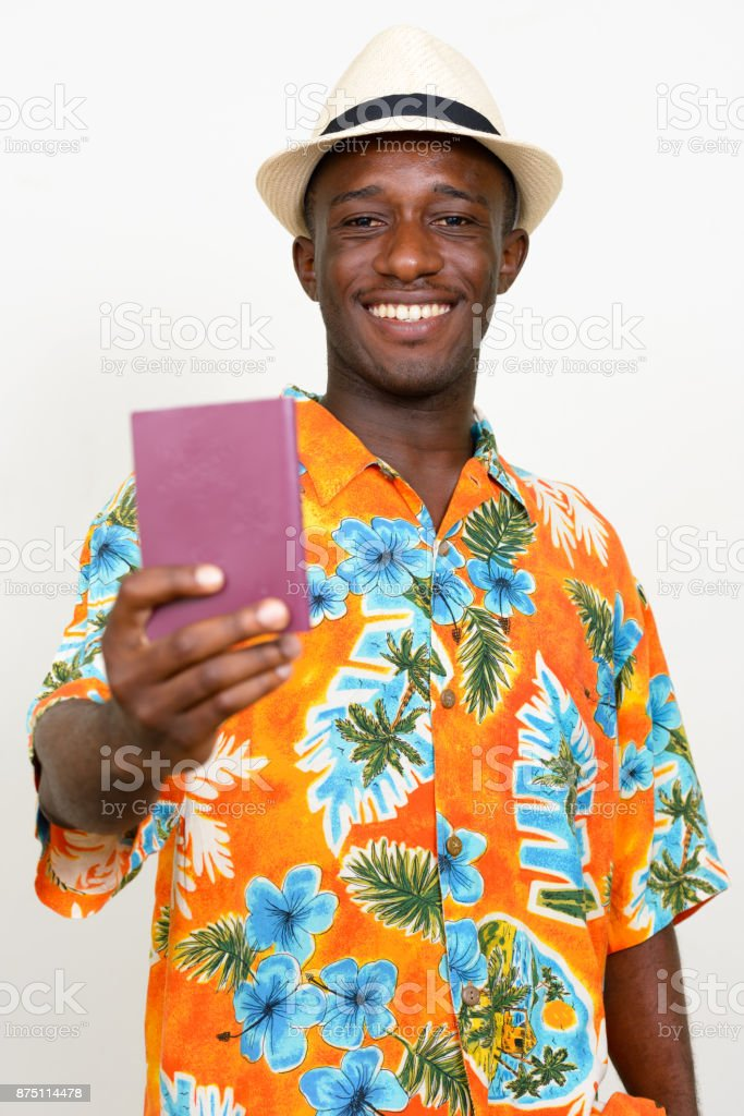 b4d846649 Young African tourist man wearing hat and Hawaiian shirt against white  background - Stock image .