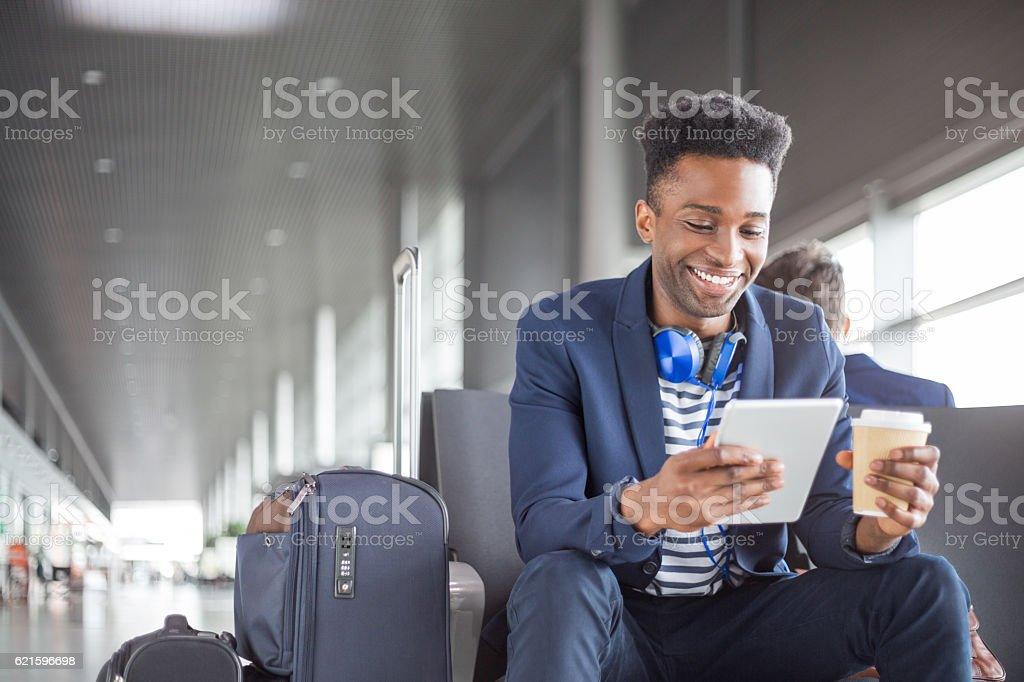 Young african using digital tablet airport lounge стоковое фото