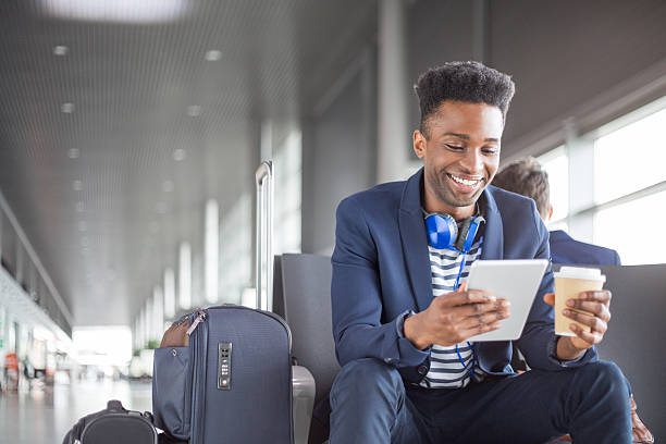 Young african using digital tablet airport lounge stock photo