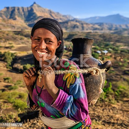 Young African woman is carring water to her house, African women and children often walk long distances to bring back jugs of water that they carry on their back.