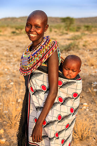 young african woman carrying her baby, kenya, east africa - kenyan culture stock photos and pictures
