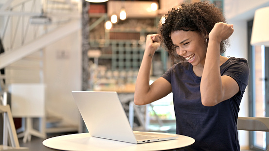 Young African Woman Celebrating Success on Laptop in Cafe