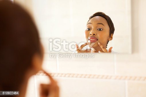 istock young african woman checking for pimple on her face 510922484