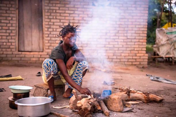 junge afrikanische Frau kocht Mahlzeit auf dem Boden – Foto
