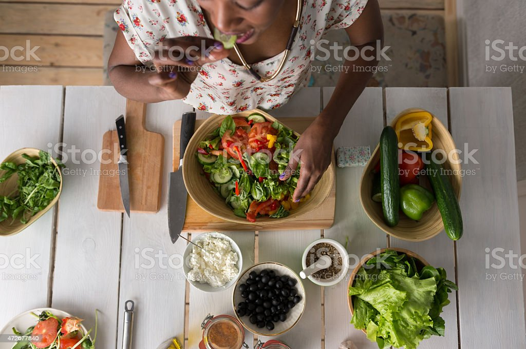 Young African Woman Cooking Salad stock photo