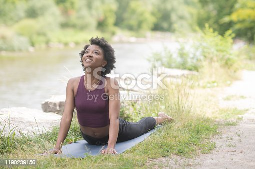 A young beautiful African woman is outside along a river doing Yoga on her mat.  She is wearing active wear and holding a Cobra pose as she smiles and enjoys her time relaxing and meditating outside.