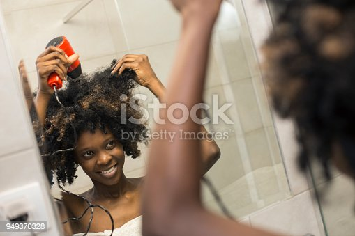 Young woman drying her hair. About 25 years old, African female.