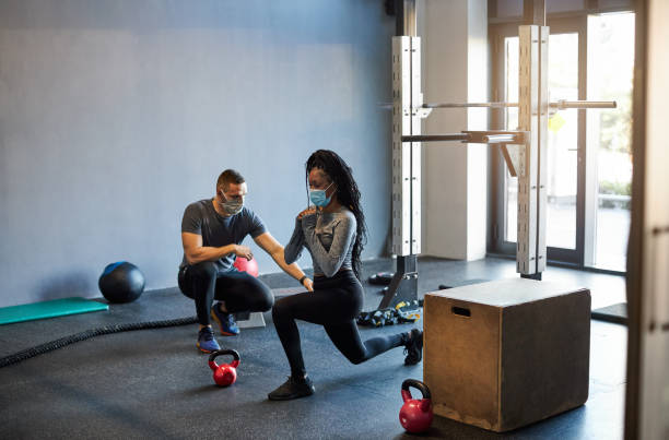 Young African Woman Exercising In The Gym With Assistance From Her Personal Trainer During Coronavirus Pandemic stock photo
