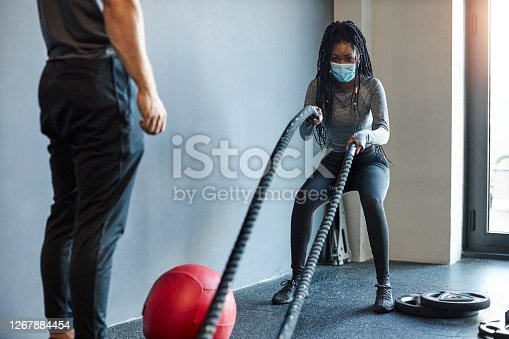 Young African woman training with roper in the gym with face mask during coronavirus pandemic. Her personal trainer is beside her.
