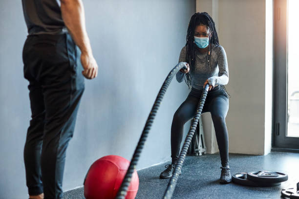 Young African Woman Exercising With Ropes In The Gym With Assistance From Her Personal Trainer During Coronavirus Pandemic stock photo