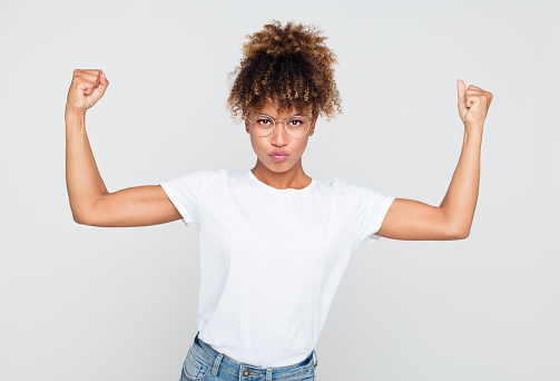 657442382 istock photo Young african woman flexing her biceps 1127917613