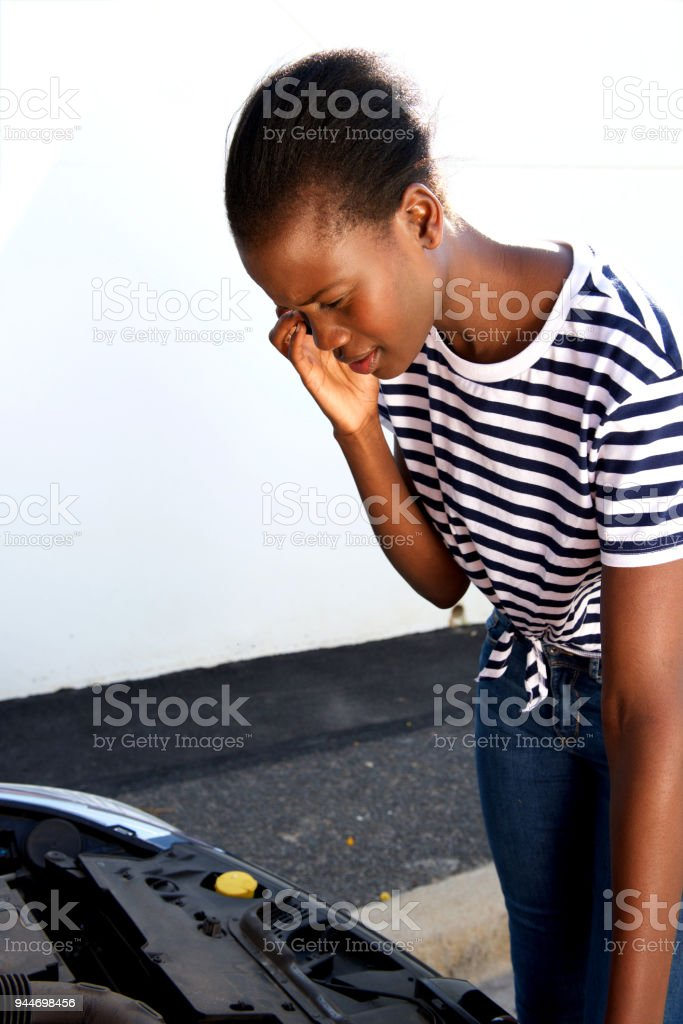 young african woman having trouble with her broken car calling for help on cell phone stock photo