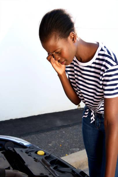 jeune femme africaine des ennuis avec sa voiture cassée, appelle au secours sur téléphone portable - Photo