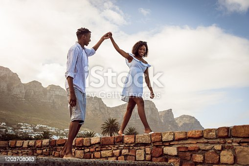 Young African couple having fun on the beach. Young woman walking along wall holding boyfriend's hand.