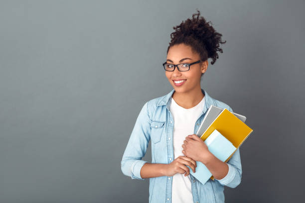 Young african woman isolated on grey wall studio casual daily lifestyle student holding notebooks smiling Young african female student isolated on grey wall wearing eyeglasses holding notebooks looking camera smiling public building stock pictures, royalty-free photos & images