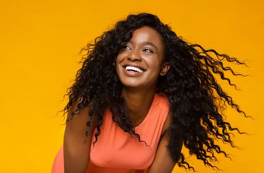 Youth and happiness. Young african woman laughing on yellow background