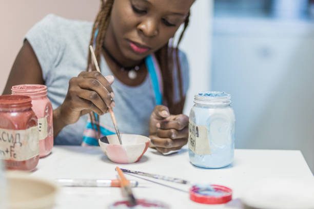 Young African woman learning ceramic art stock photo