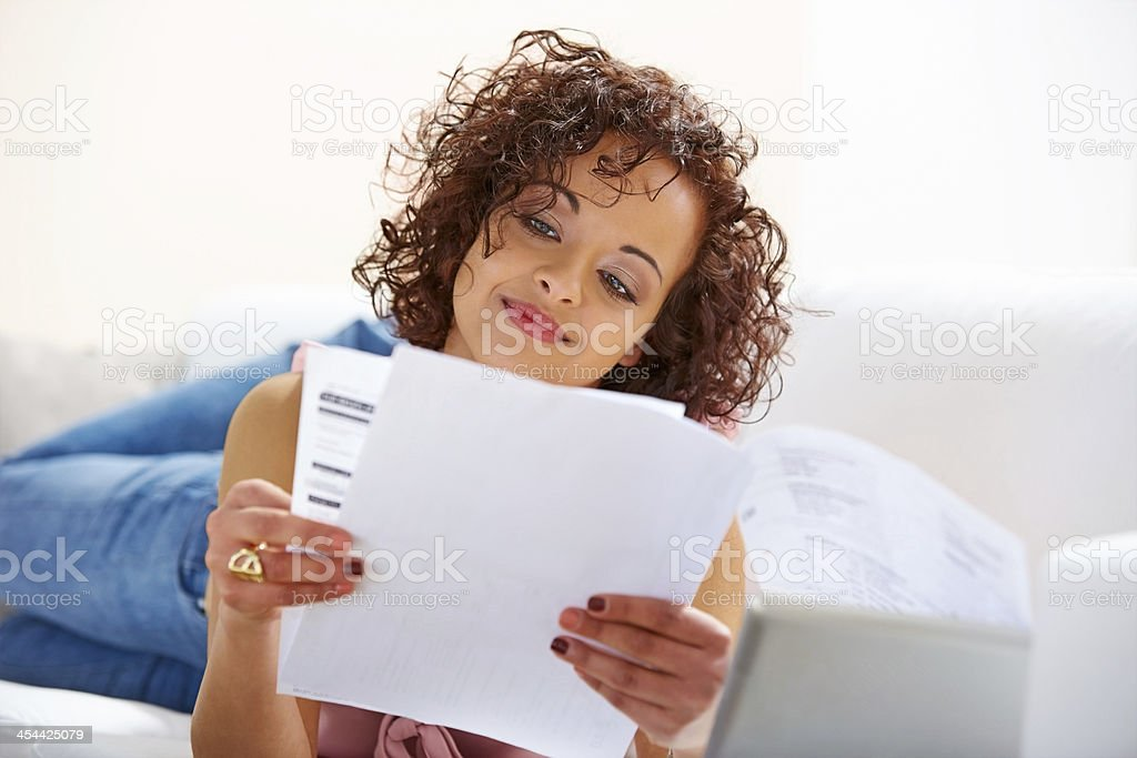 Young African woman looking at her monthly expenses bills stock photo