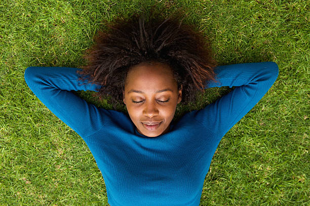 Young african woman lying on grass sleeping stock photo