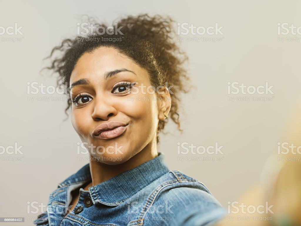 Young african woman making a funny face and taking selfie stock photo
