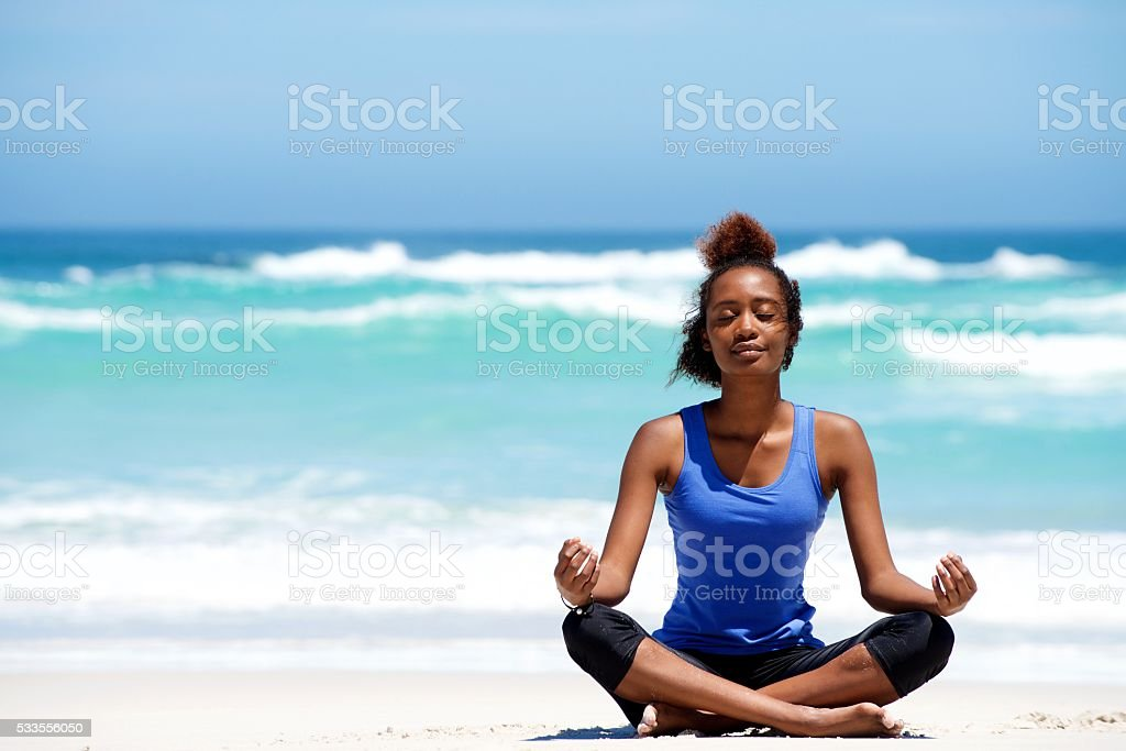 Young african woman meditating in yoga pose at the beach stock photo
