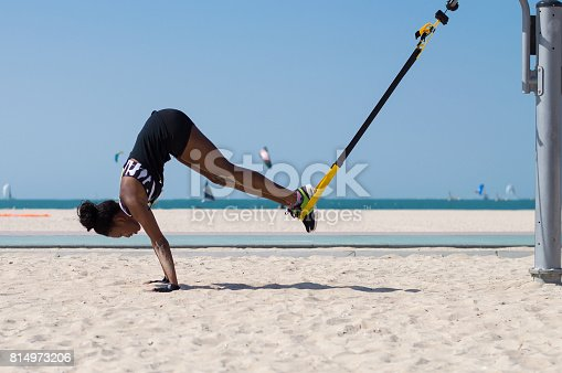 istock Young african woman performing exercise using ropes for suspension training 814973206