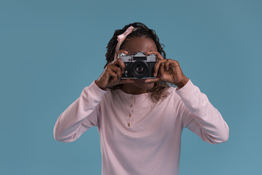 istock Young african woman photographing 615416504