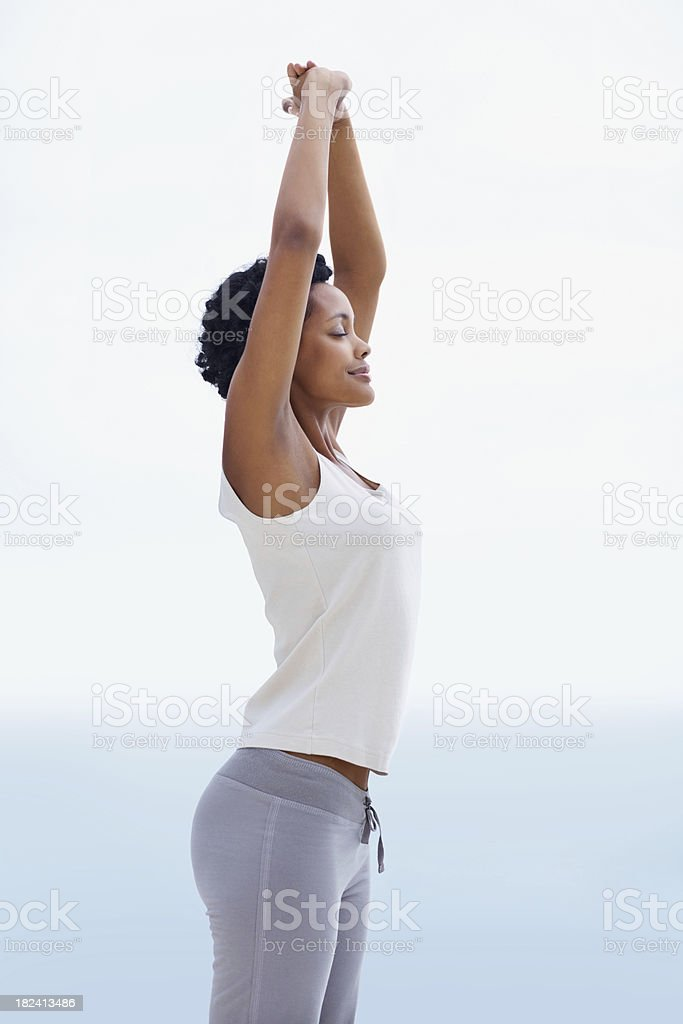 Young African woman practicing yoga with hands together royalty-free stock photo