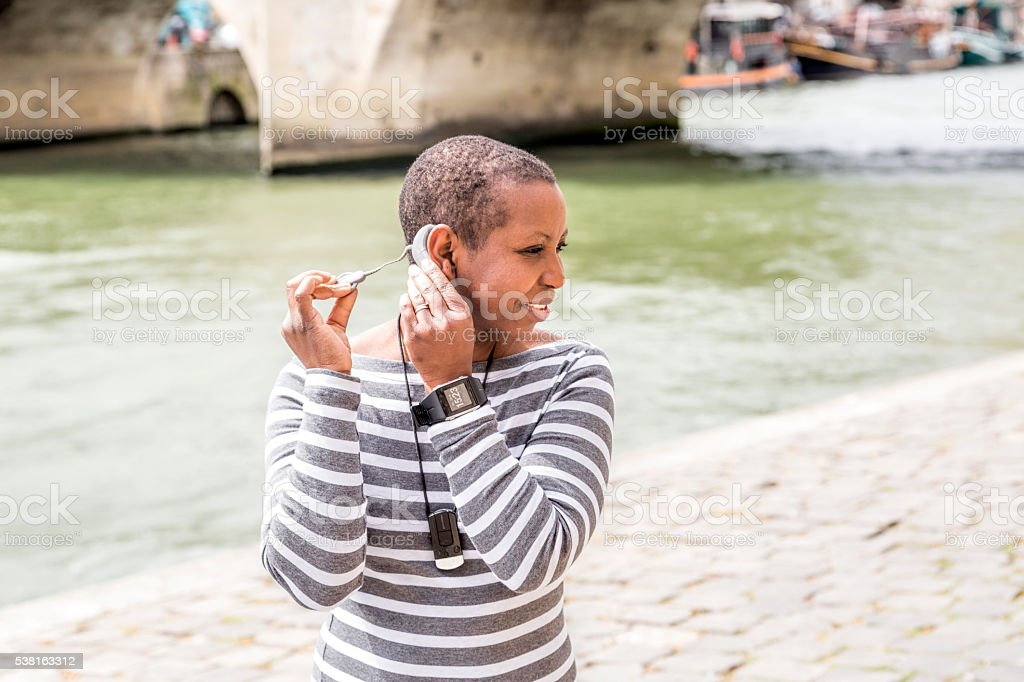 Young African woman putting on cochlear implant processor. Paris spring. stock photo