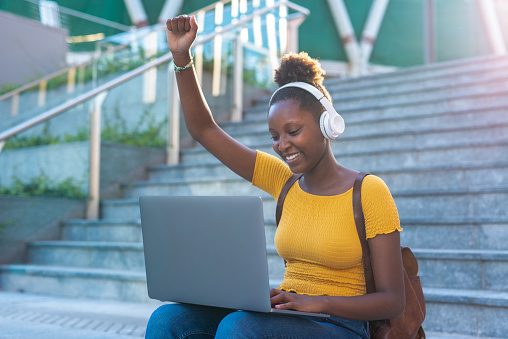 young african woman raises her fist to exult in success, student satisfied with her results, fashion woman with laptop, sunset light in background, fight for equality