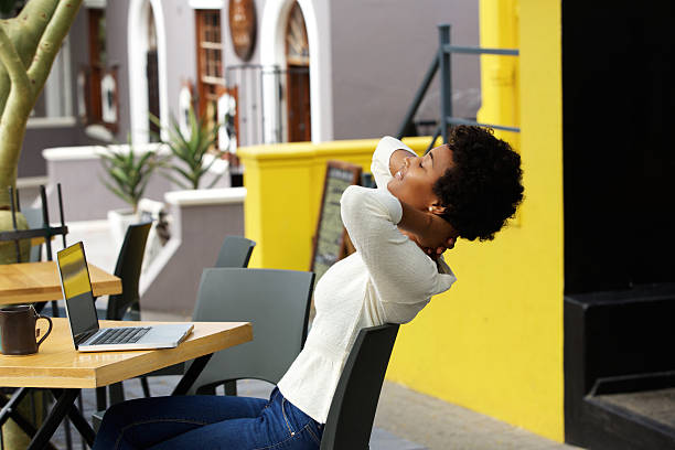 Young african woman relaxing at outdoor cafe stock photo