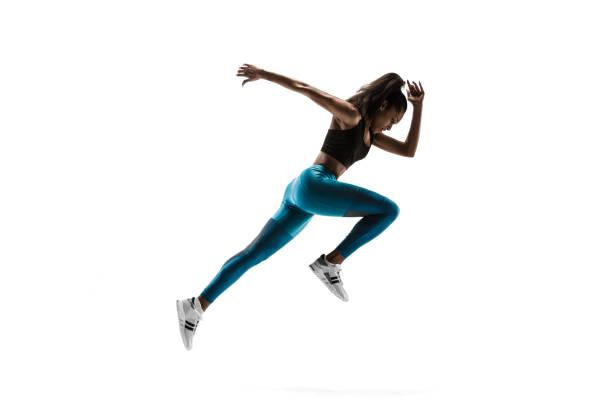 jonge afrikaanse vrouw hardlopen of joggen geïsoleerd op witte studio achtergrond. - atleet stockfoto's en -beelden