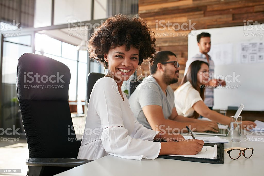 Young african woman sitting at a business presentation stock photo