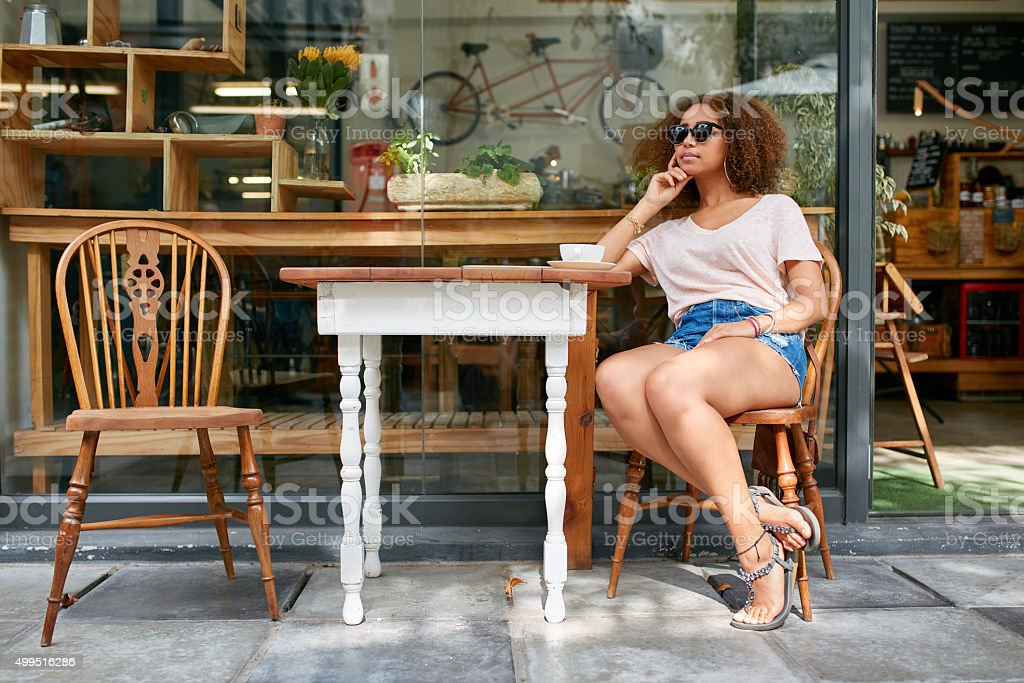 Young african woman sitting at coffee shop stock photo