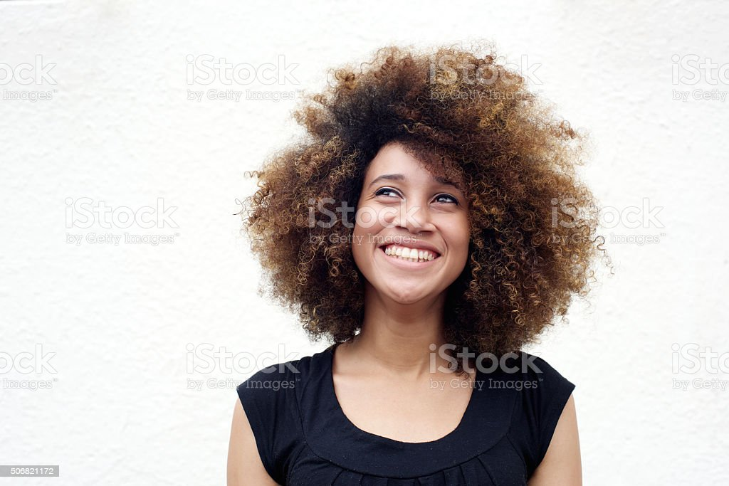 Young african woman smiling and looking up stock photo