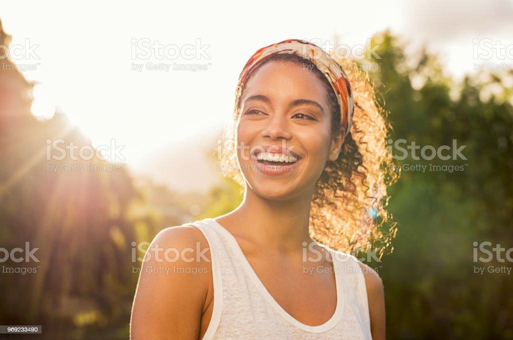 Jovem mulher africana sorrindo ao pôr do sol foto de stock royalty-free