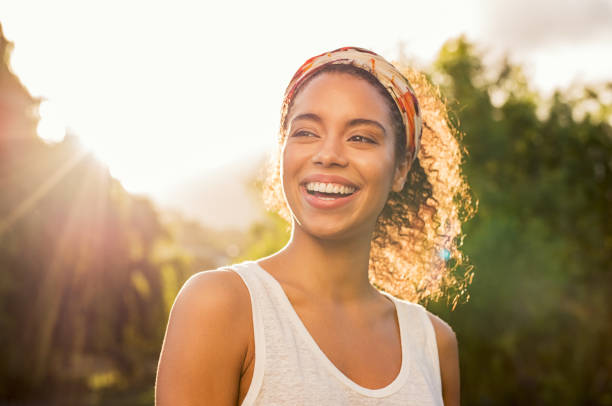 Young african woman smiling at sunset stock photo