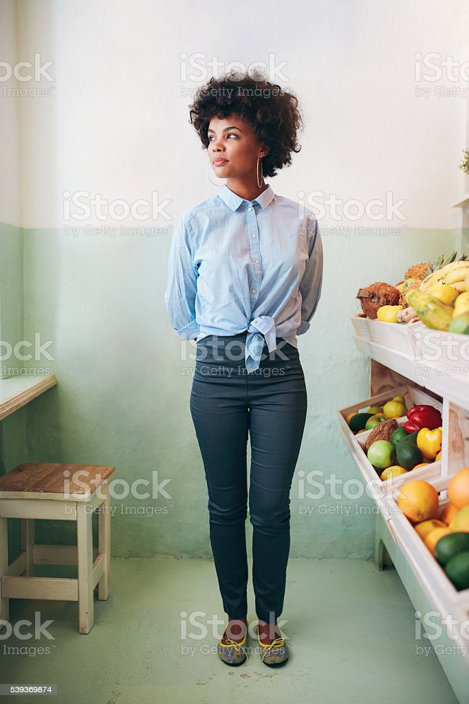 Young african woman standing in a juice bar стоковое фото