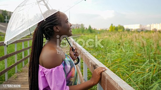 Young african woman under transparent umbrella in rainy weather on the bridge.