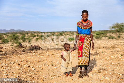 Young African mother from Samburu tribe walking with her baby , Kenya, Africa. Samburu tribe is one of the biggest tribes of north-central Kenya, and they are related to the Maasai.