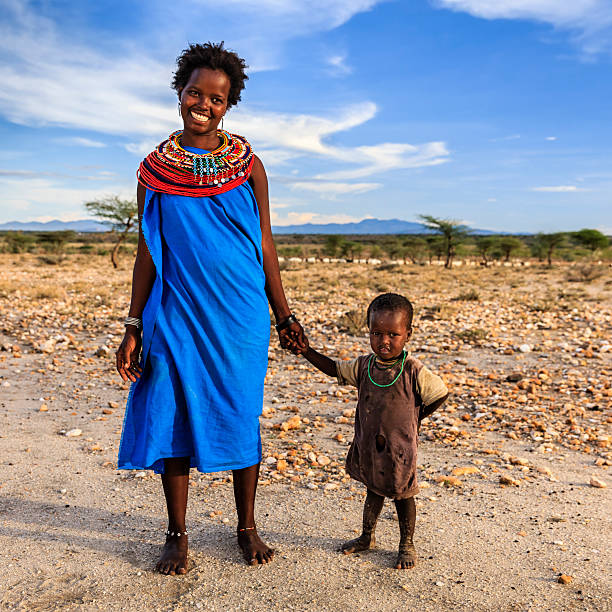 young african woman walking with her baby, kenya, east africa - kenyan culture stock photos and pictures