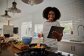 istock Young african woman watching recipe in digital tablet while cooking lunch in modern kitchen 1253249134
