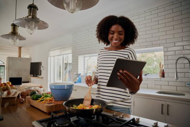 giovane donna africana guardando ricetta in tablet digitale durante la cottura del pranzo in cucina moderna - cucinare foto e immagini stock