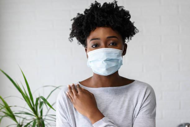Junge afrikanische Frau trägt eine chirurgische Gesichtsmaske – Foto