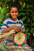 Young African woman weaving food basket in Ethiopia, East Africa