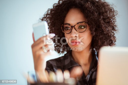 Close up of young african woman with glasses reading text message on her mobile phone at office