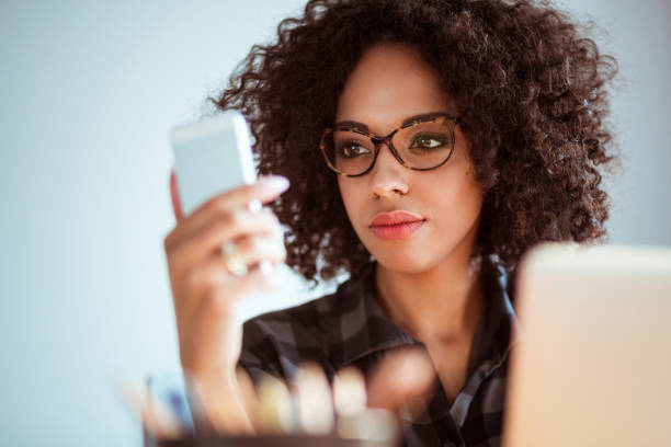 Young african woman with glasses using mobile phone stock photo