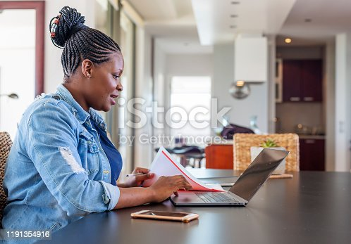 Young African Woman Working at Home on a Laptop Computer at the Dining Room Table
