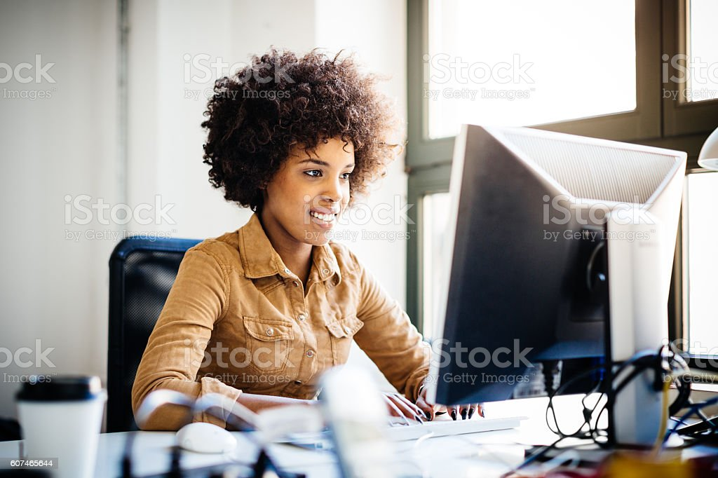 Young African Woman Working in Loft Space Behind Computer - Photo